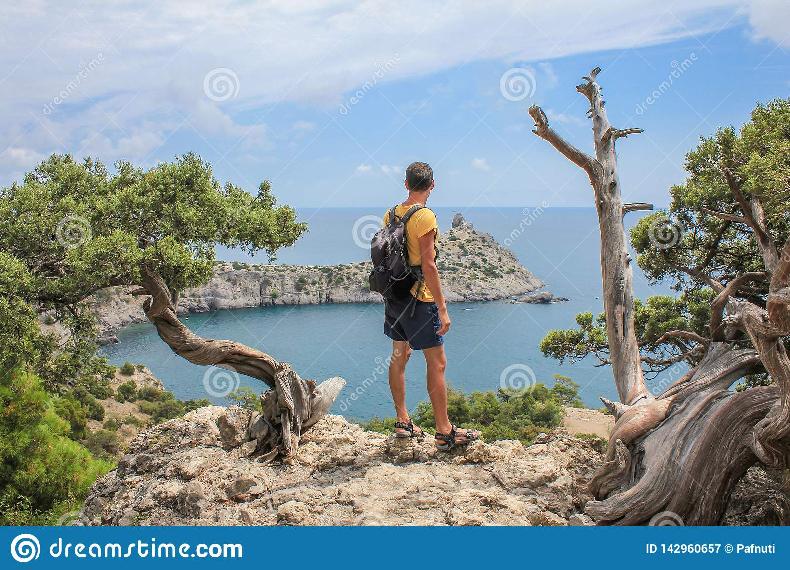 Young sporty man with backpack standing on the top of rock