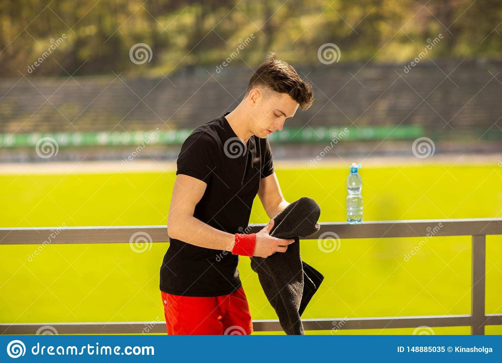 Young sporty man resting and wiping his sweat with a towel after workout sport exercises outdoors