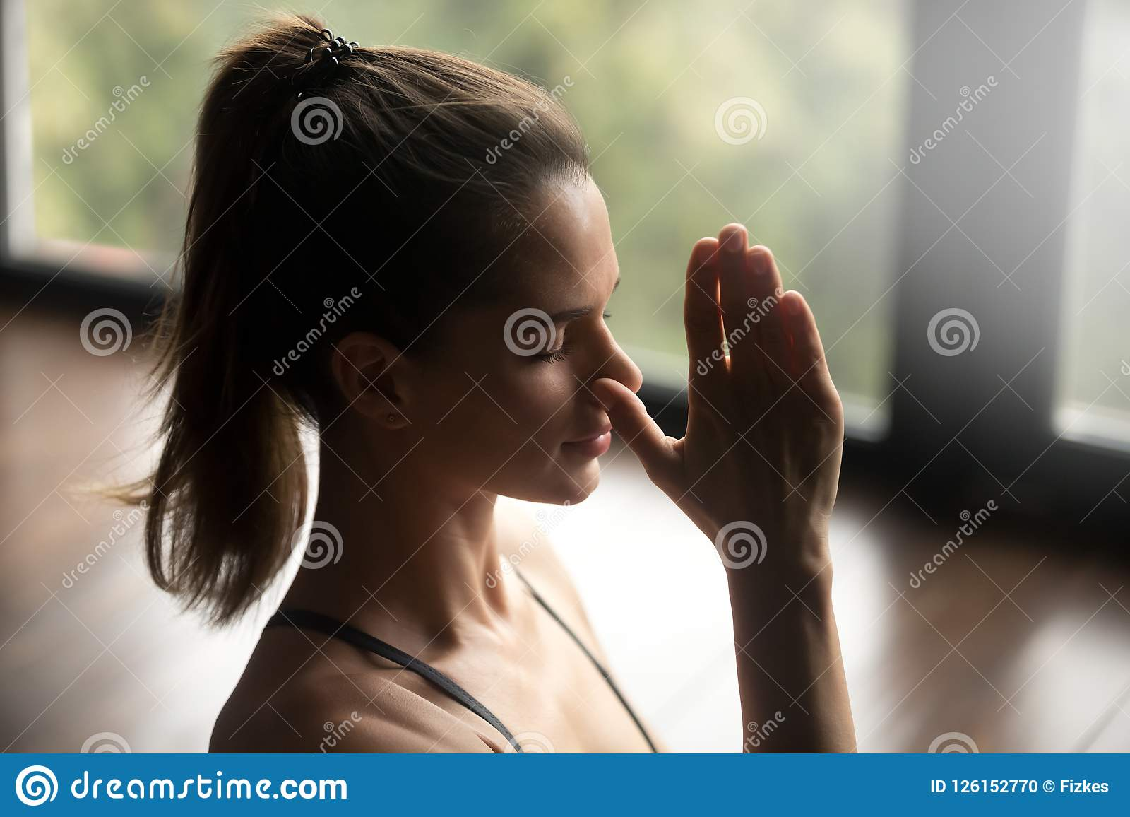 Young sporty woman in Alternate Nostril Breathing