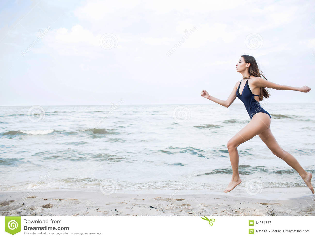 a612245d79 Young sporty woman with dark long hair in a blue bathing suit running on a  beach. Summer photo concept. Sport photo concept.