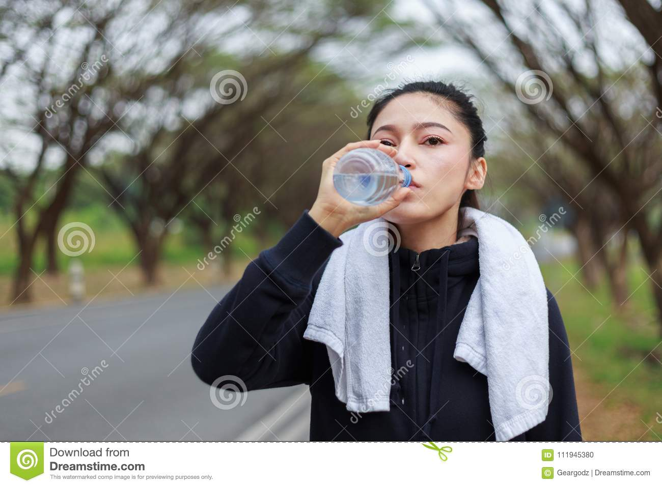 Young Sporty Woman Drinking Water In Park Stock Photo