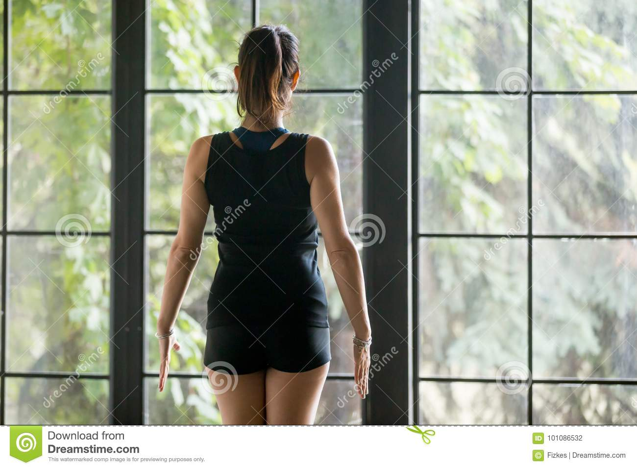 Young sporty woman in mountain pose, window background, rear vie