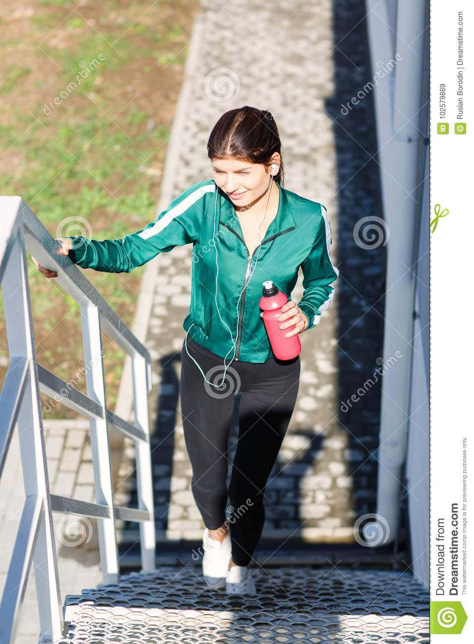 A young sporty woman with perfect body doing exercises on stairs outdoor.
