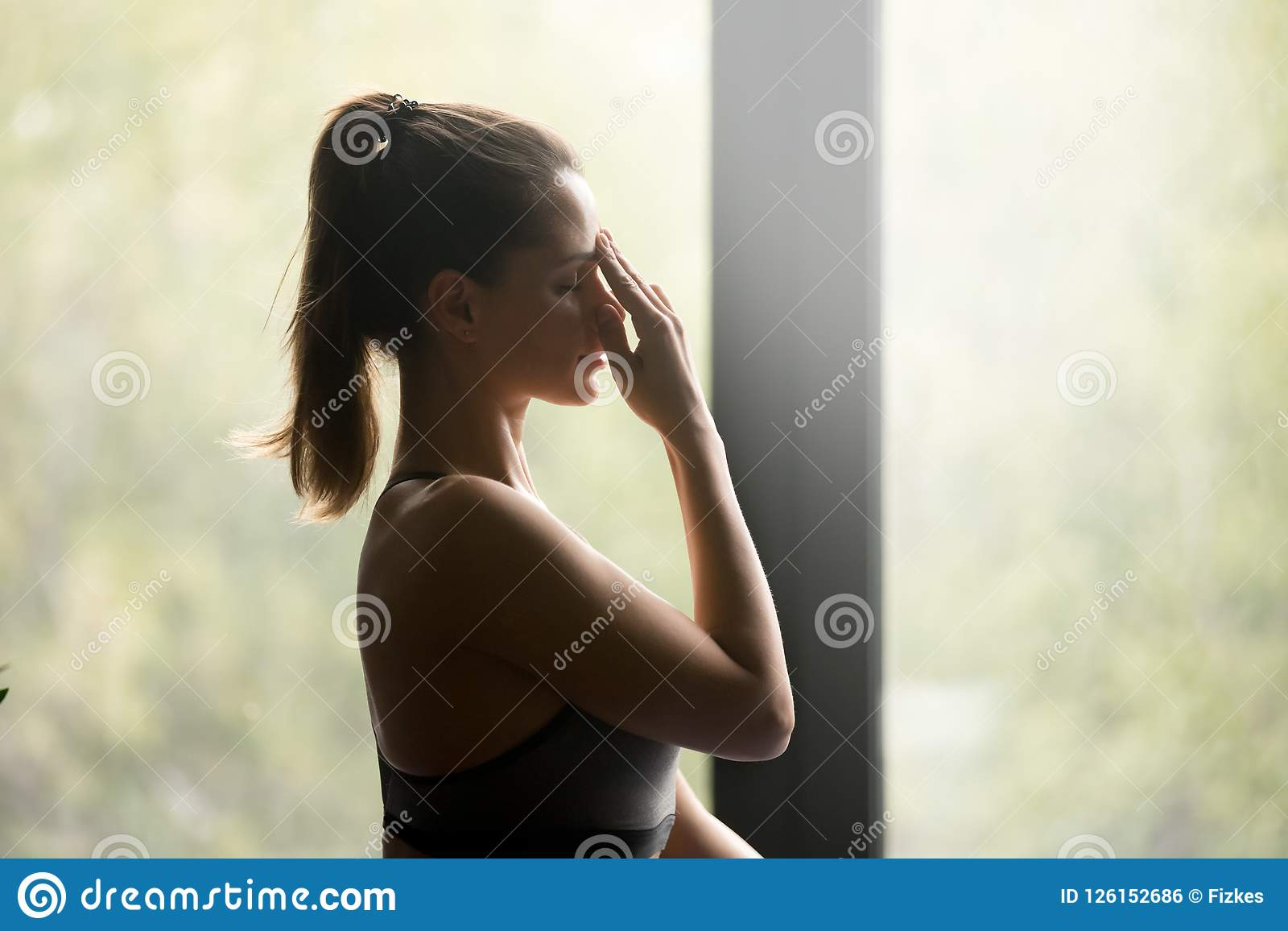 Young sporty woman doing Alternate Nostril Breathing