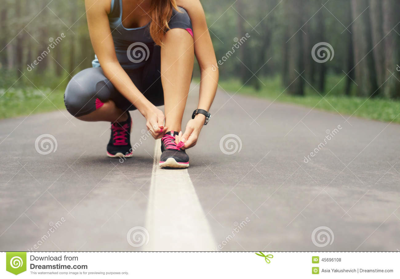 Young sporty woman preparing to run in early foggy morning in th