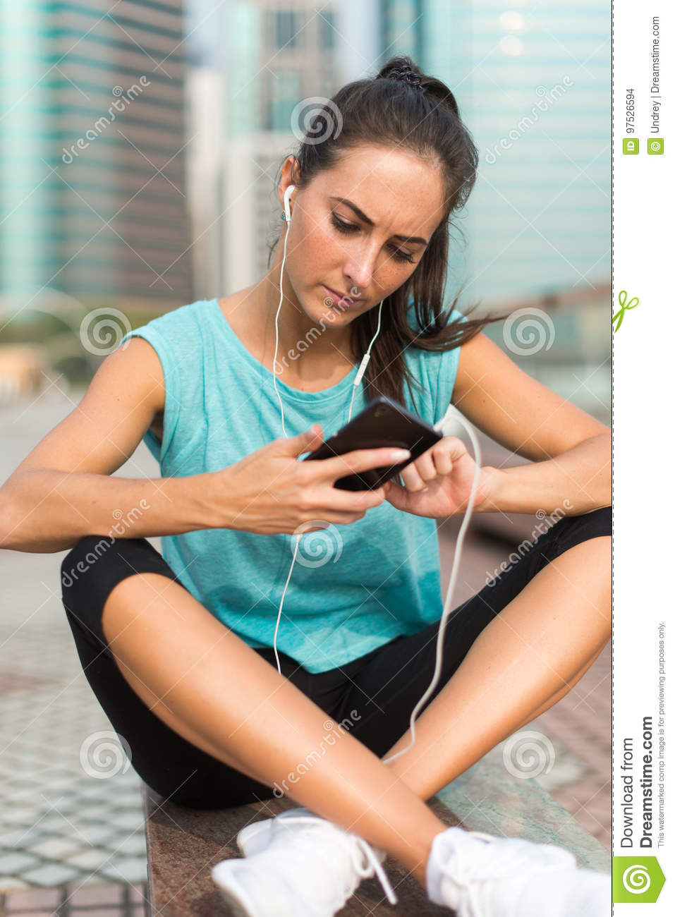 Young sporty woman resting after exercising using her smartphone and listening to music in earphones. Athlete runner in