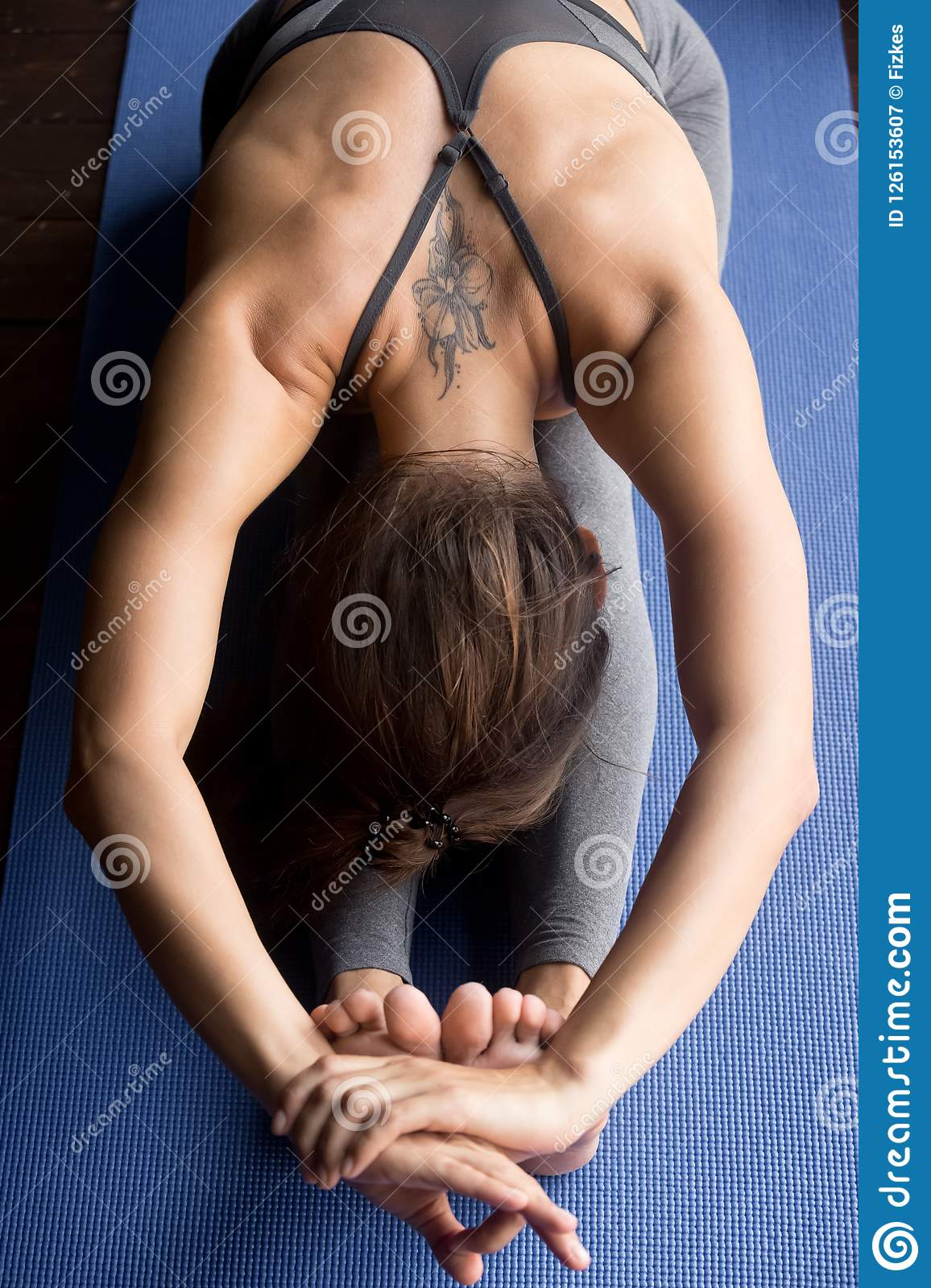Young sporty woman in Seated forward bend pose