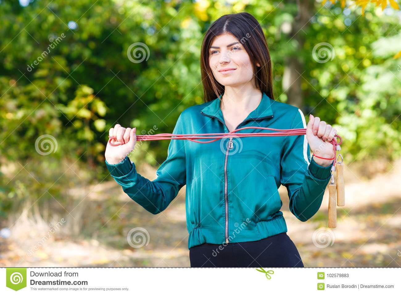 A young sporty woman with skipping rope doing exercises outdoor.