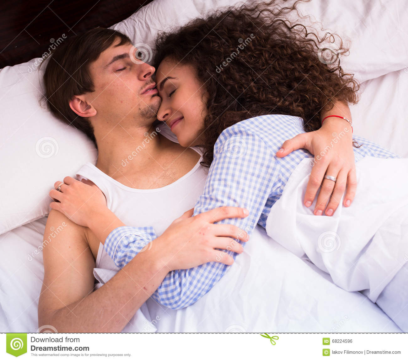 Young Spouses Hugging As Sleeping In Bed Stock Photo