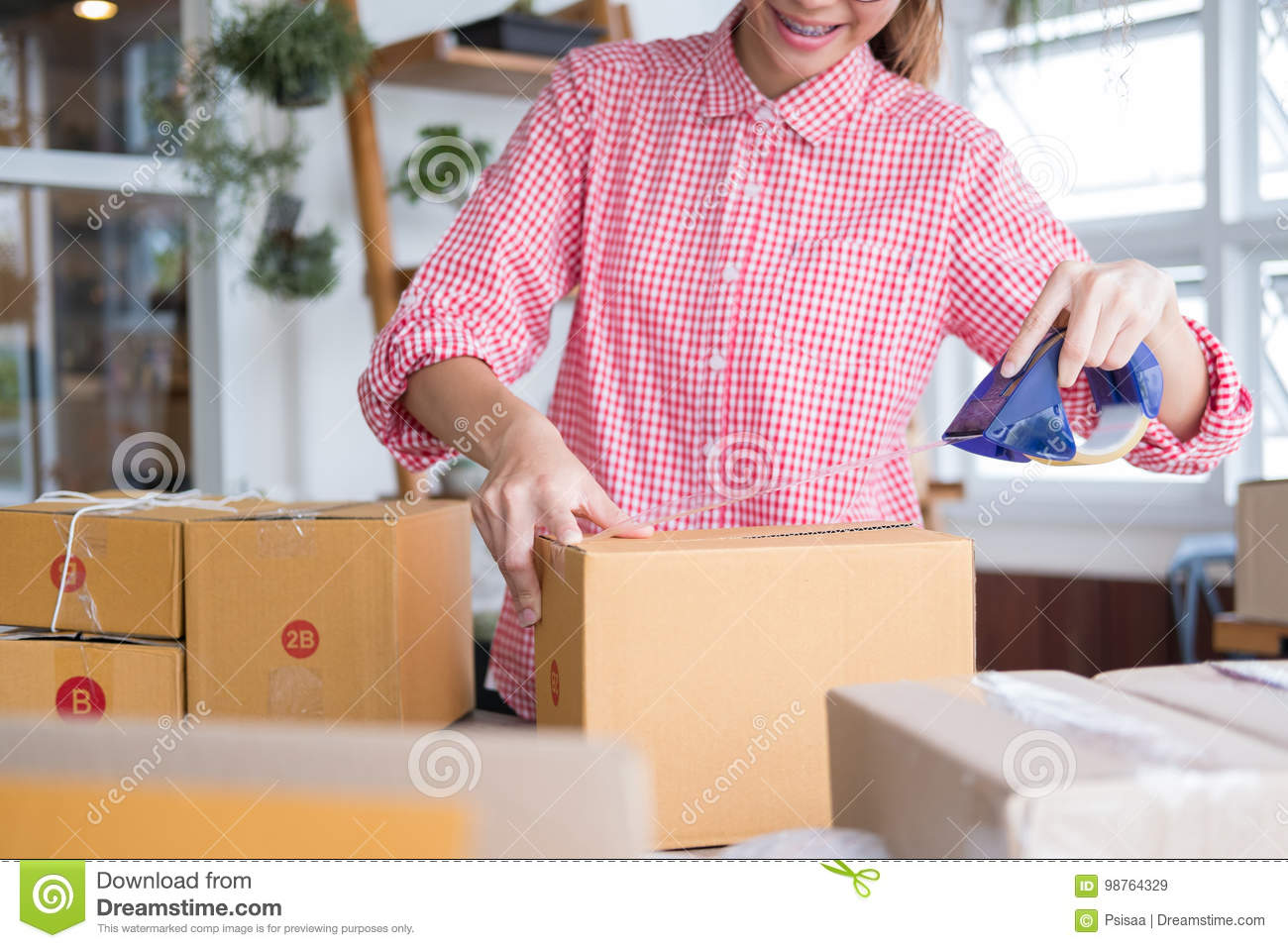 start up small business owner packing cardboard box at workplace