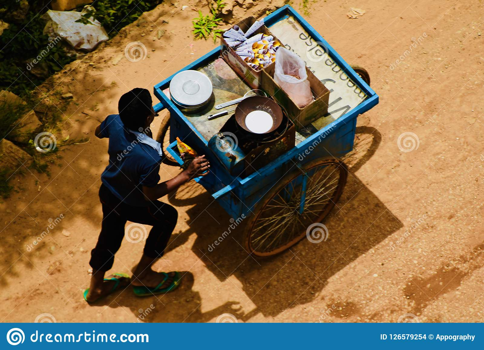 A young street food seller walking in the road in Bangalore