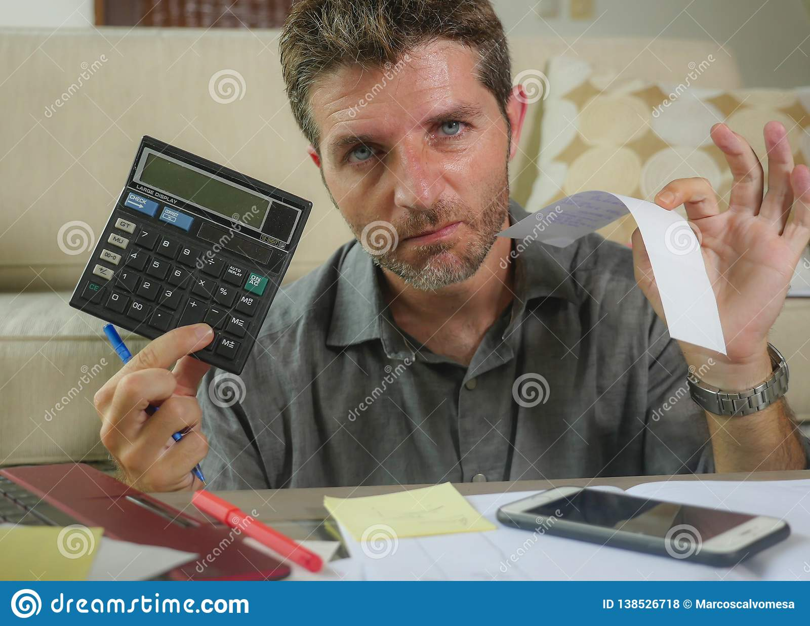 Young stressed and worried man at home living room using calculator and laptop doing domestic accounting paperwork feeling