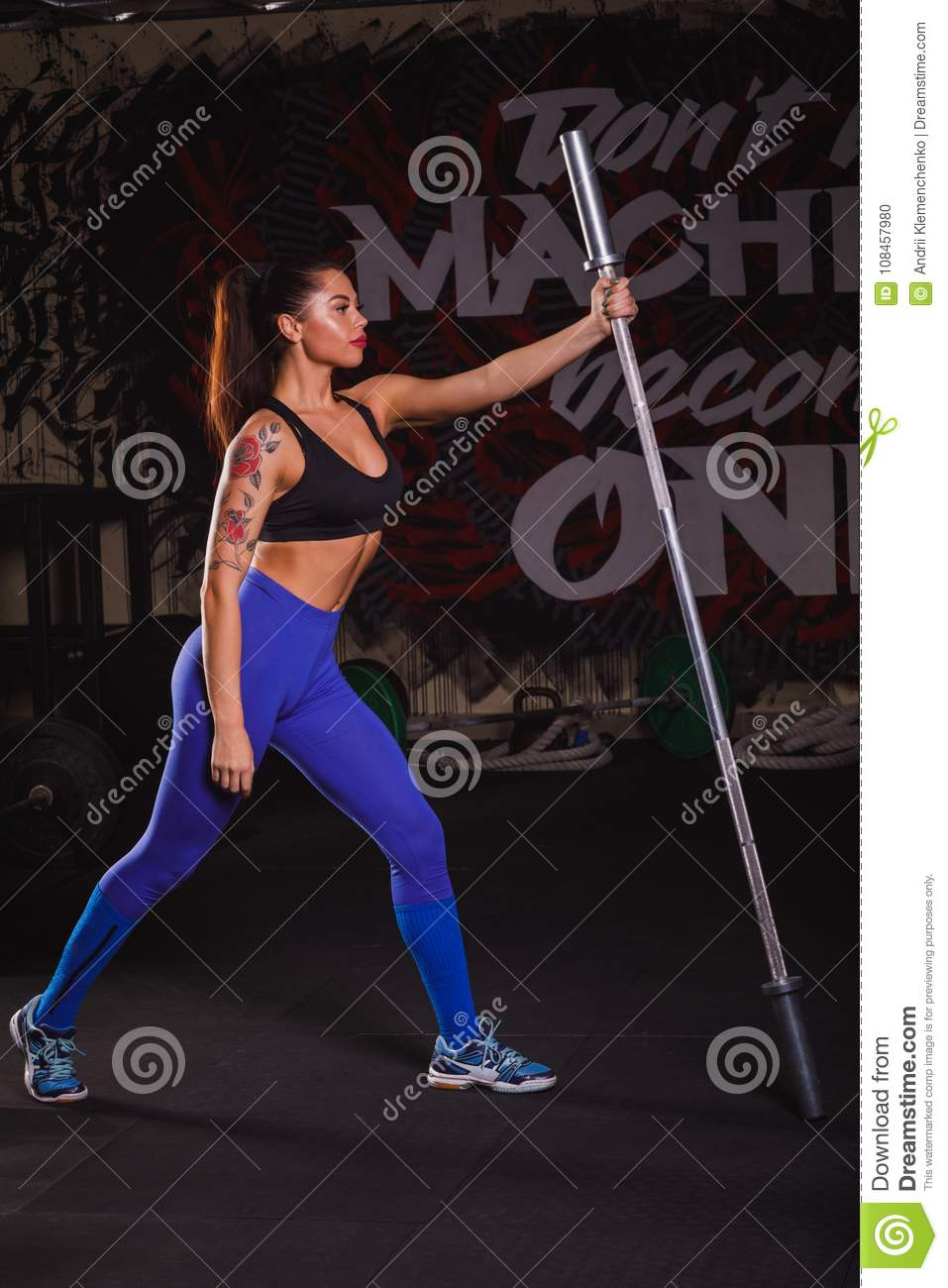 Young strong caucasian sport woman doing fitness exercises with rod. Girl execute exercise with barbell