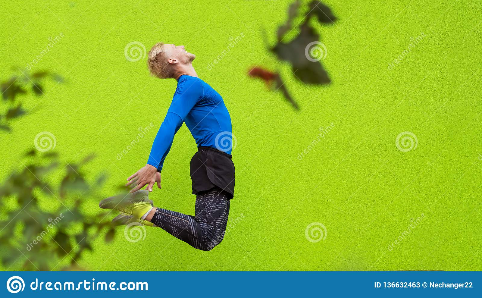 Young strong man jumping on green background