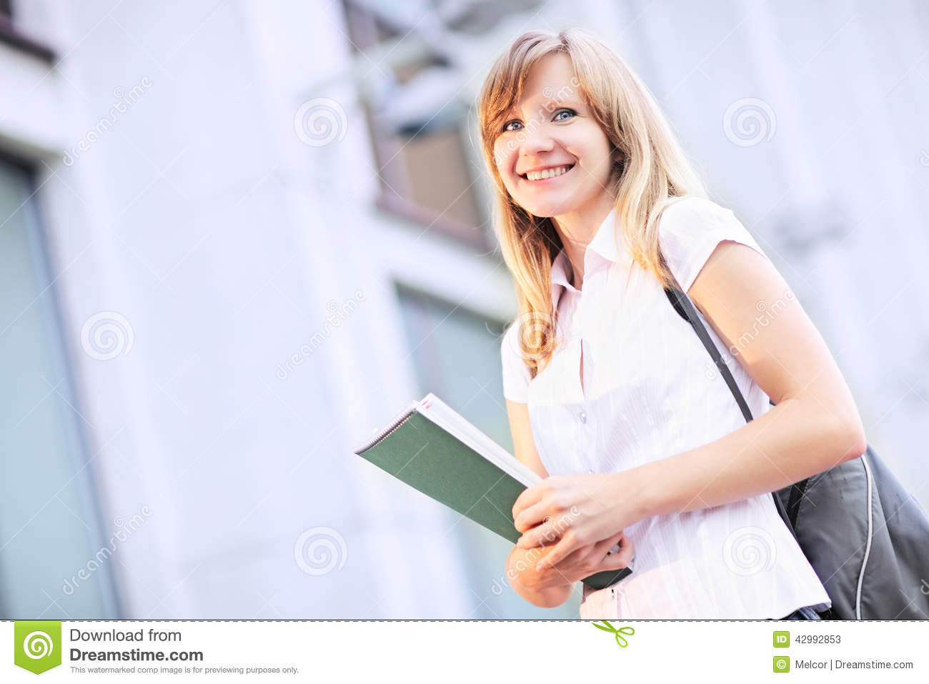 Young student, beautiful caucasian woman standing on blurred university building background in the morning.