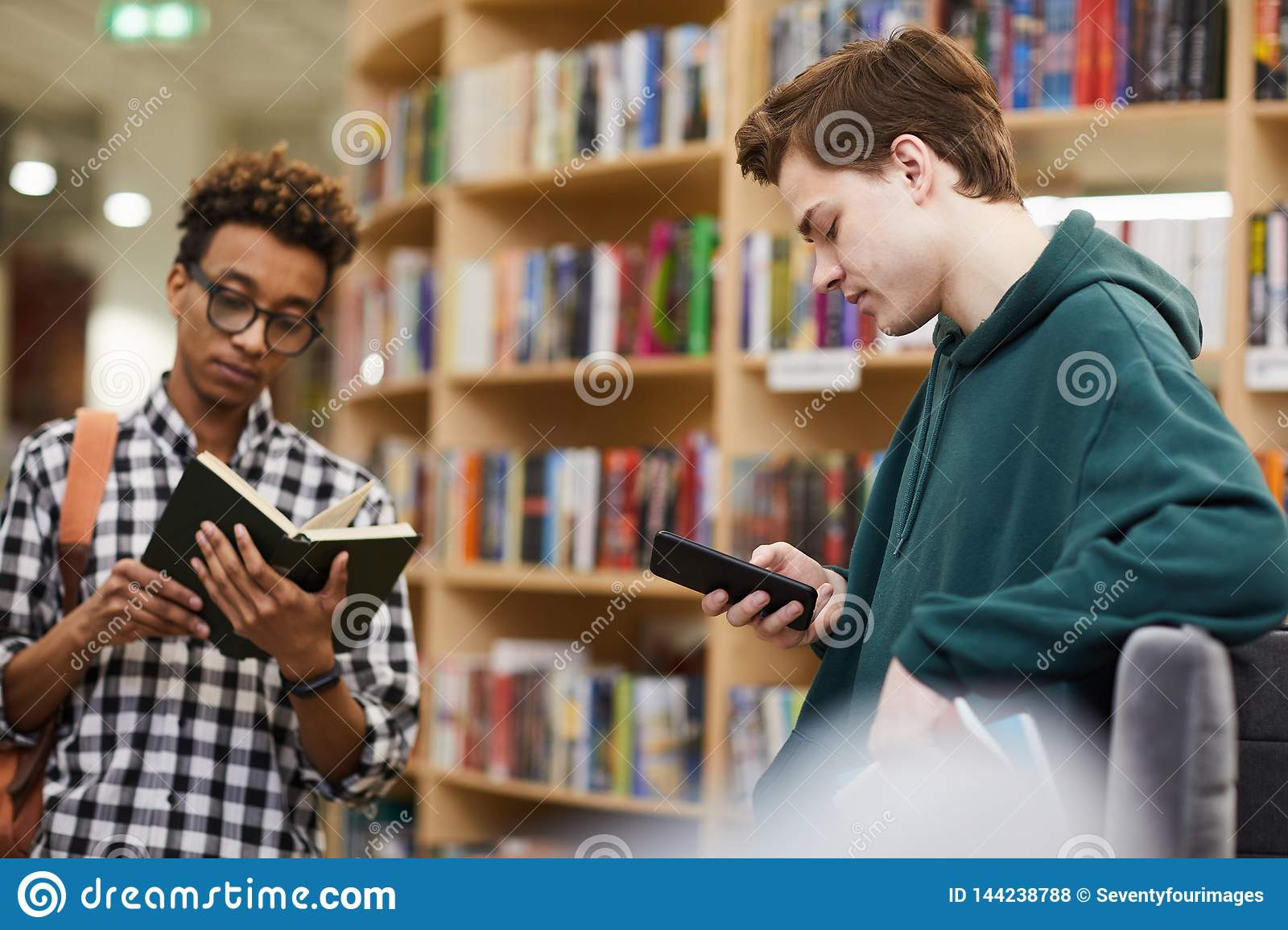 Young Student Boys Choosing Literature In Library Stock Photo - Image of  standing, message: 144238788