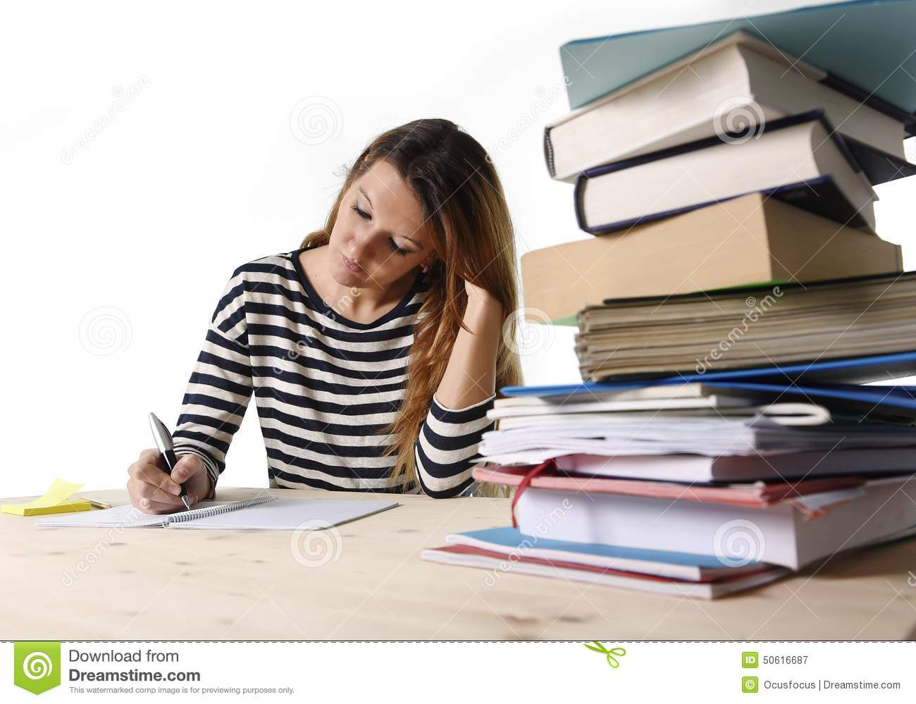 Young Student Girl Concentrated Studying For Exam At