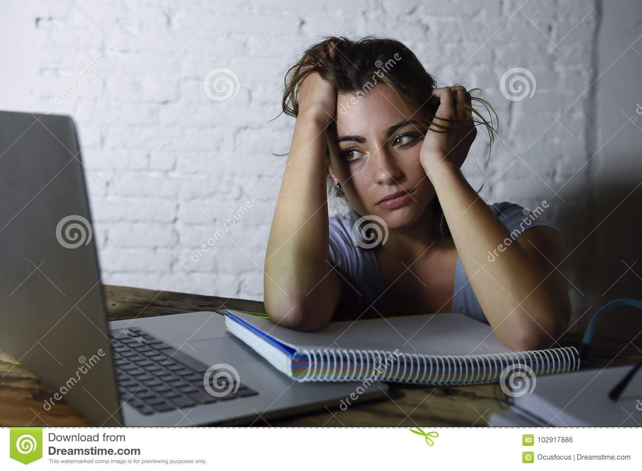 Young student girl studying tired at home laptop computer preparing exam exhausted and frustrated feeling stress