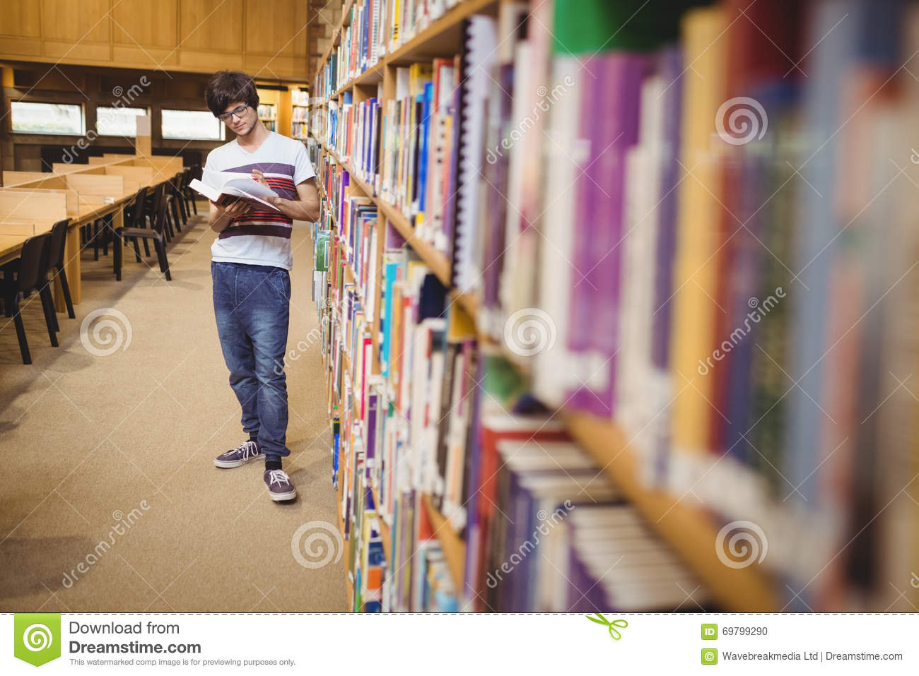 Download Young Student Reading Book While Standing Near Bookshelf Stock Photo