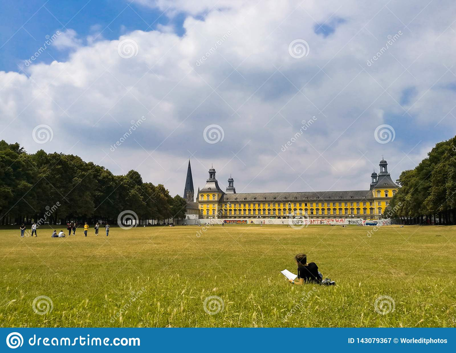 Young student resting on the grass reading a book