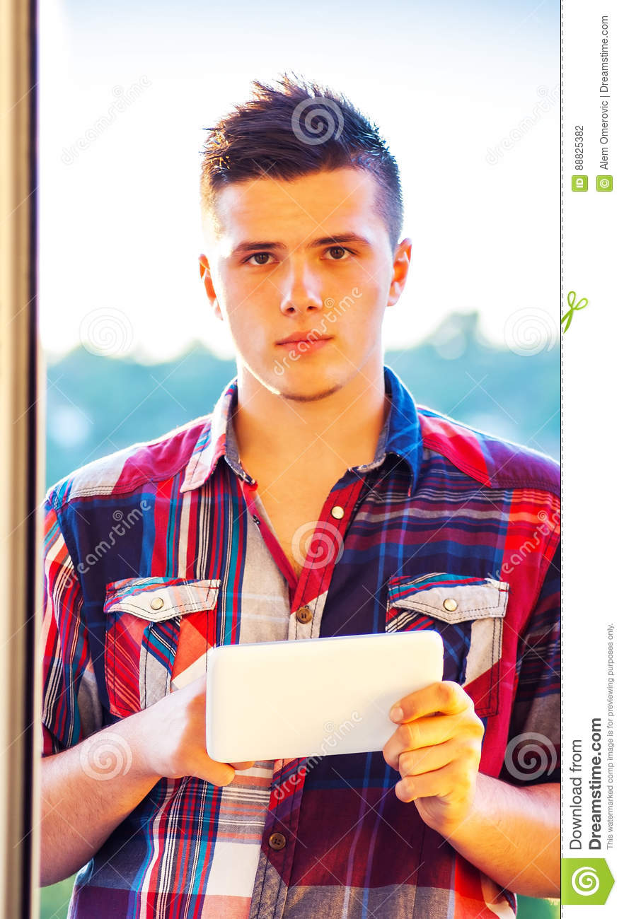 Young student using tablet outdoor at sunny day