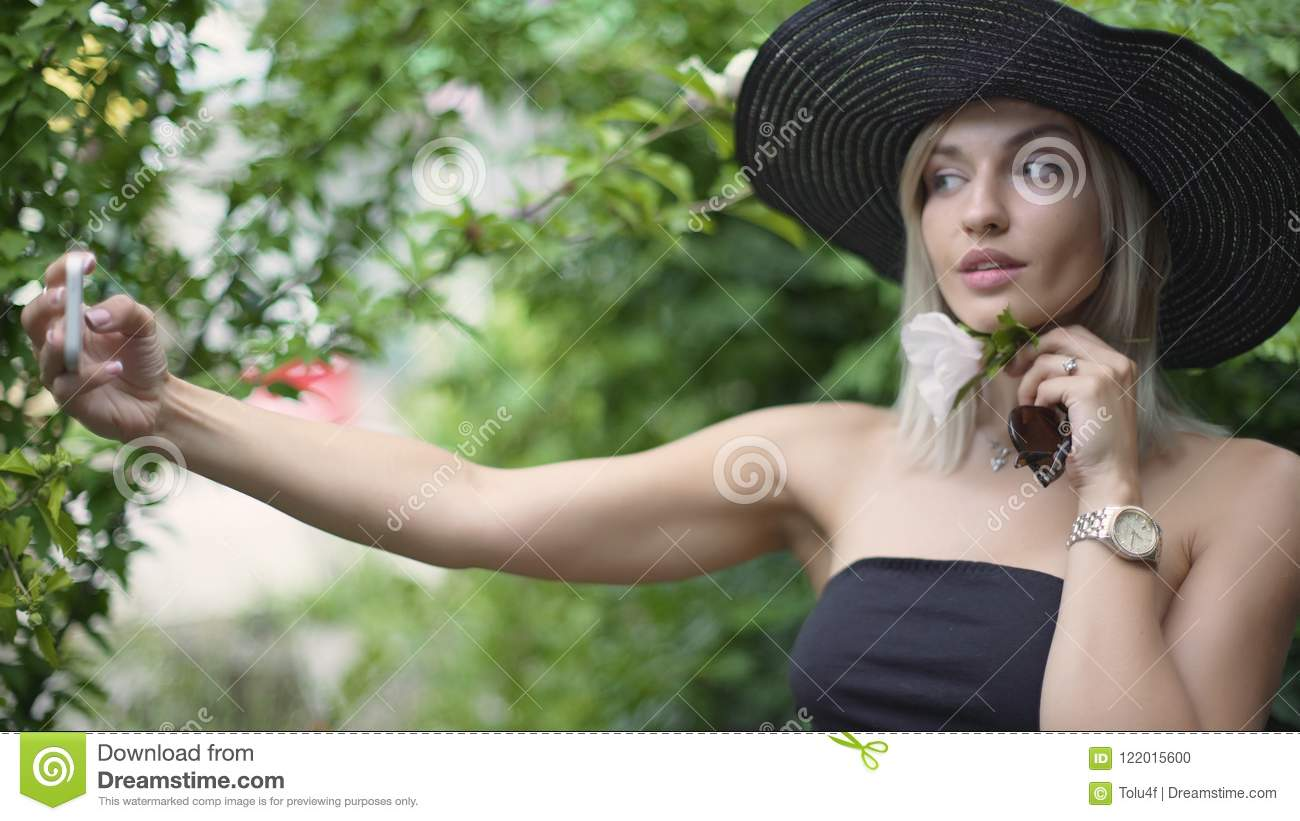 Young stylish beautiful woman in hat does selfie. Female using a smart phone