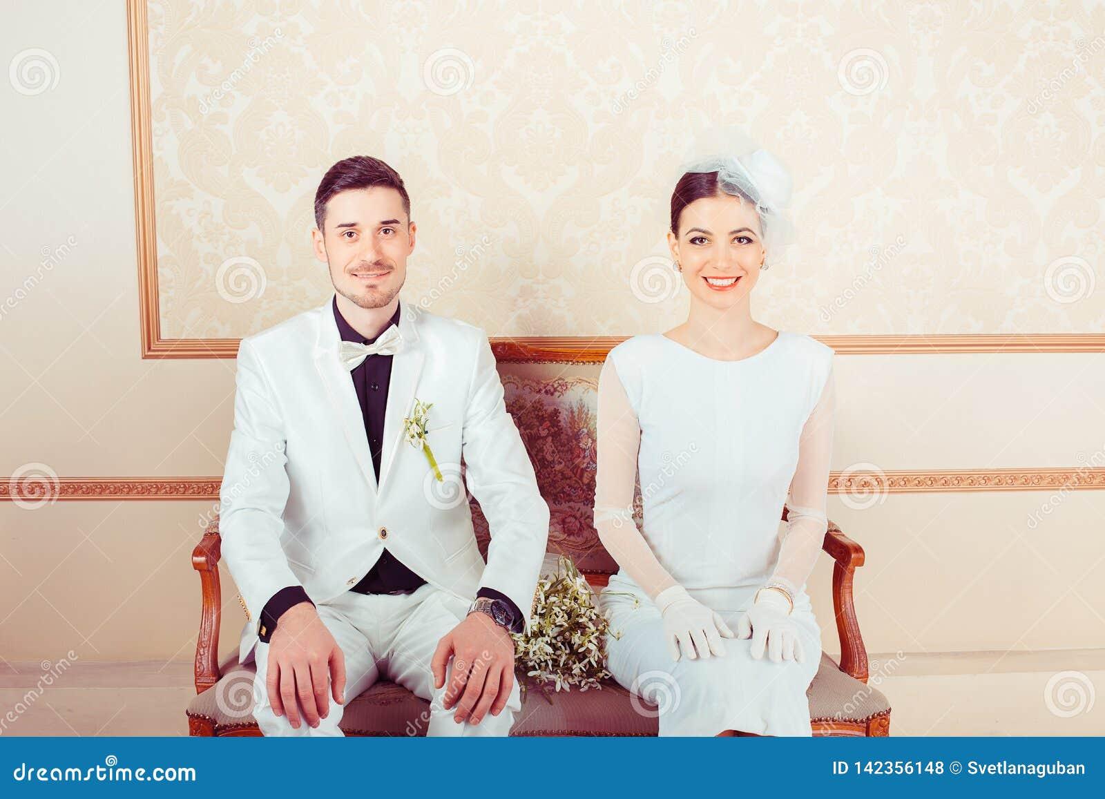 Young stylish bride and groom on sofa