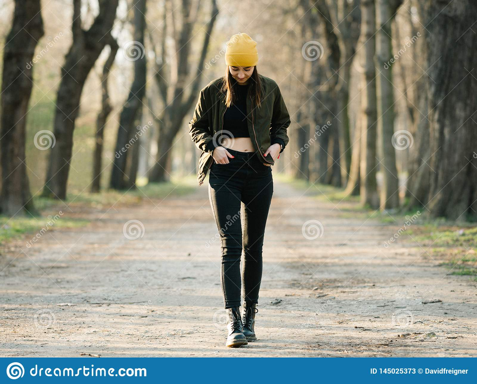 Young stylish girl with belly top walking on an avenue