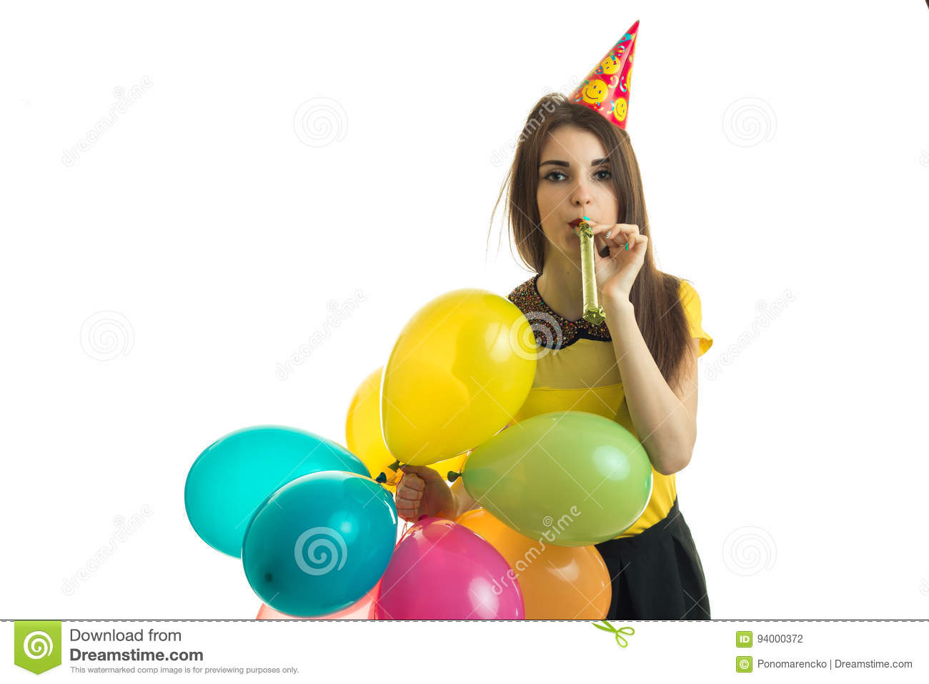 Young Stylish Girl Blowing Horn With Balloons In Her Hands On Birthday Party