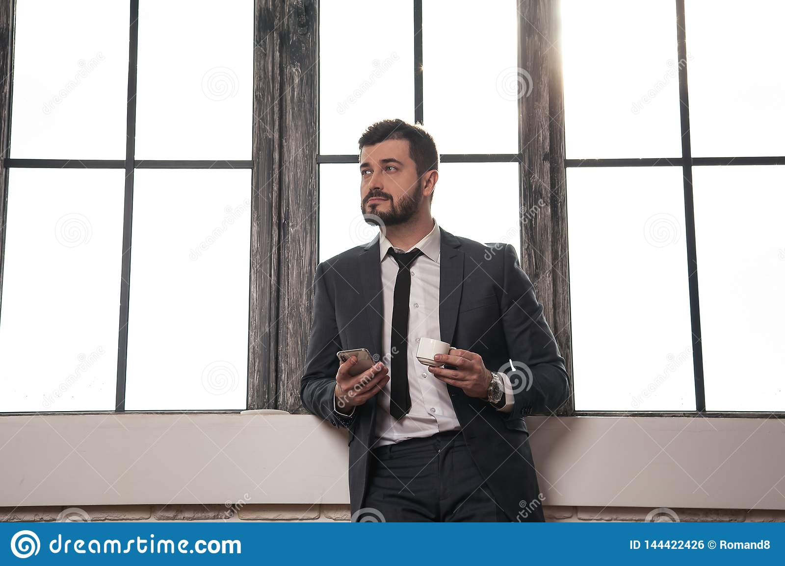 Young stylish handsome businessman is standing by the window at his office having a coffee break and holding a cell phone in his