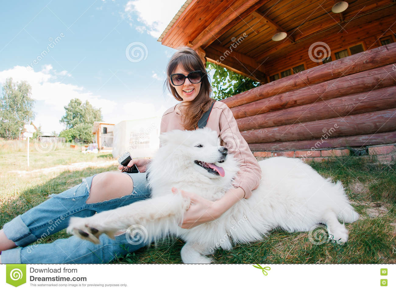 Young stylish hipster woman girl playing white kid-skin dog in country side