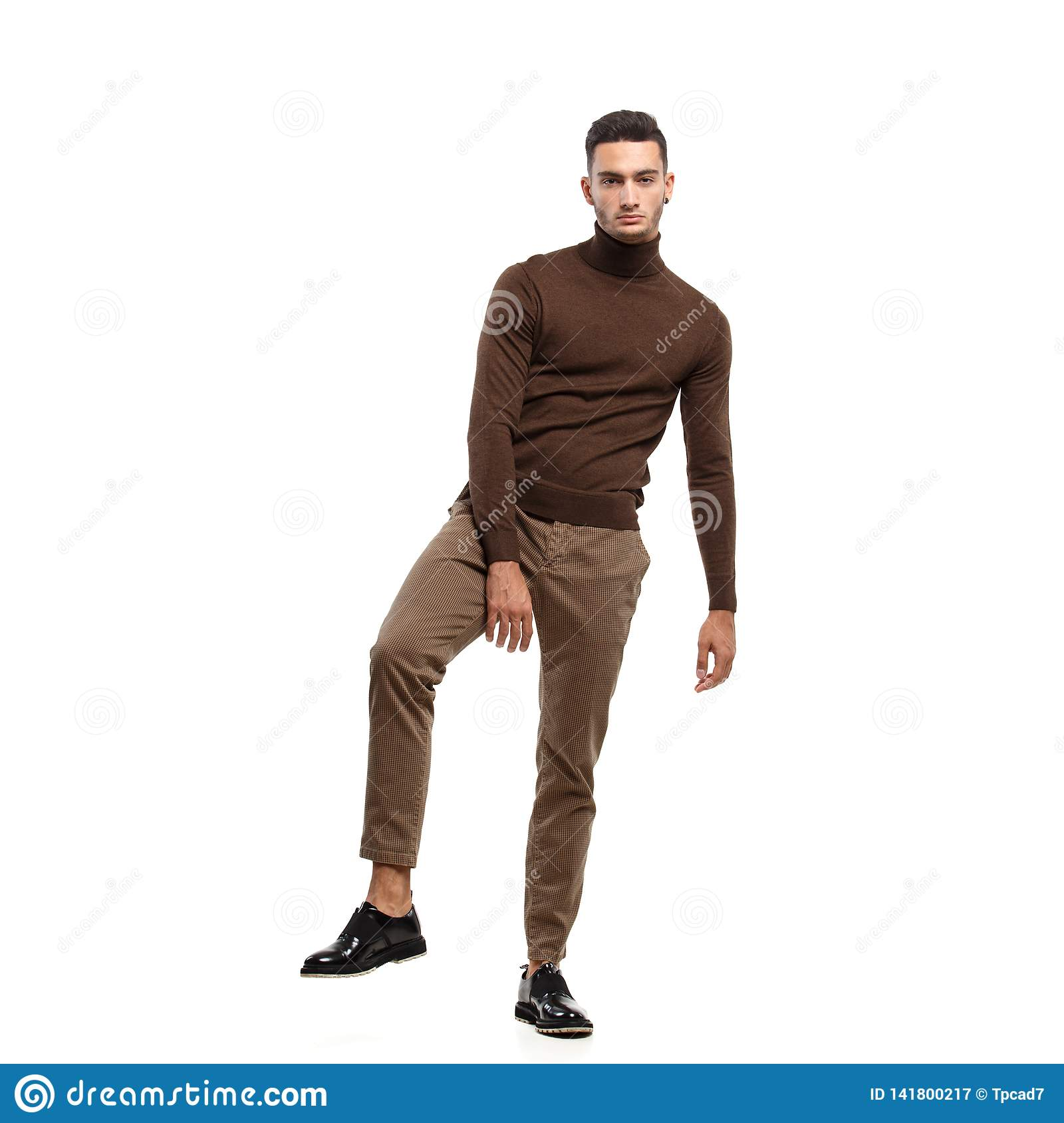 f484b417 Young stylish man dressed in brown turtleneck and pants stands on the white  background in the