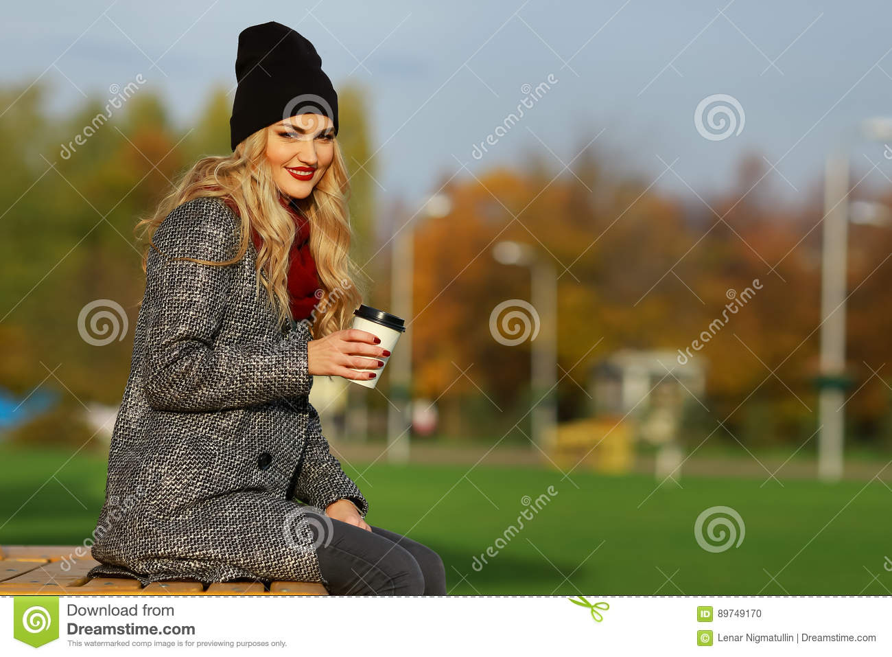 Young stylish woman smiling with coffee in a park