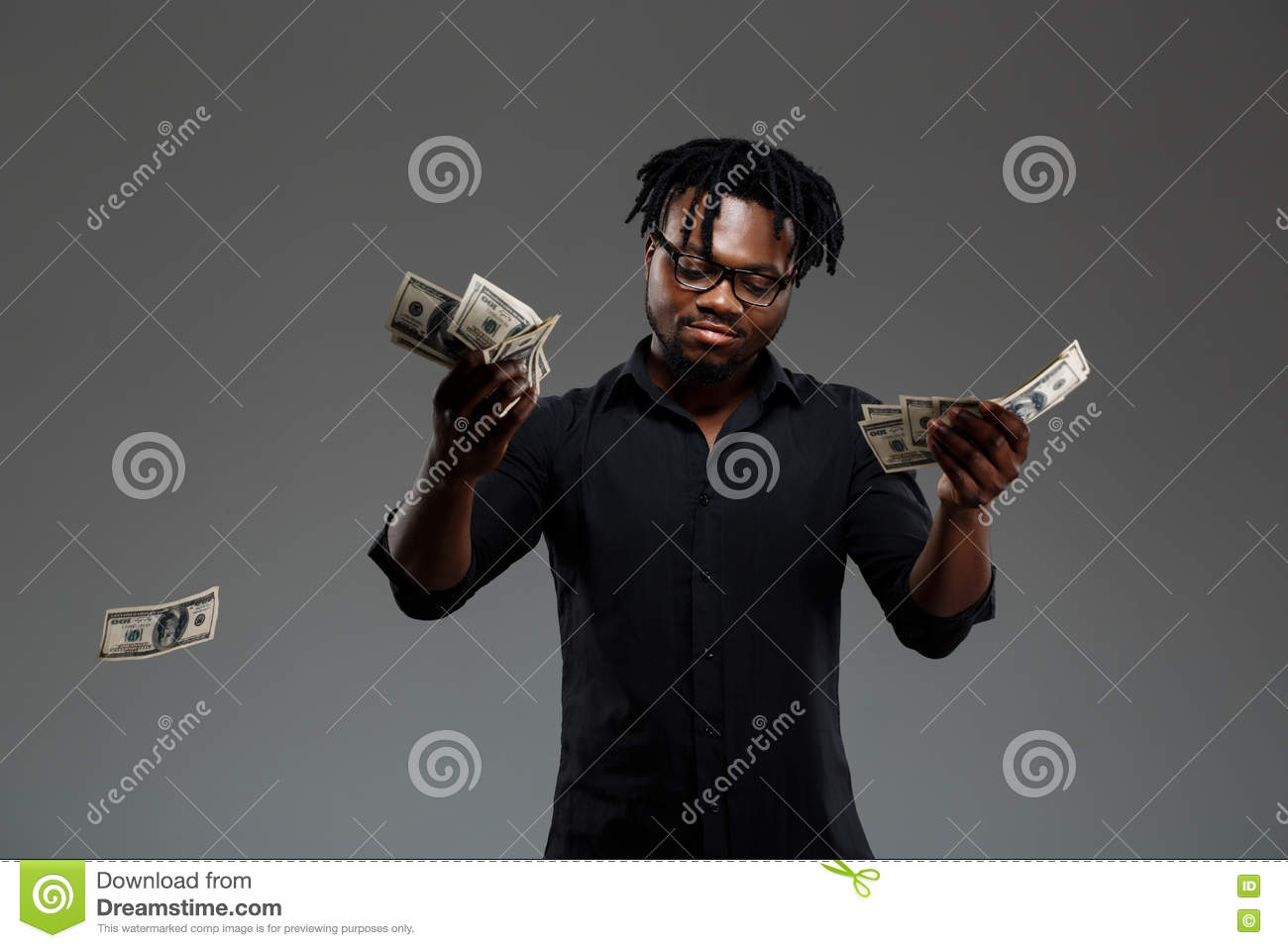Young successful african businessman throwing money over dark background.