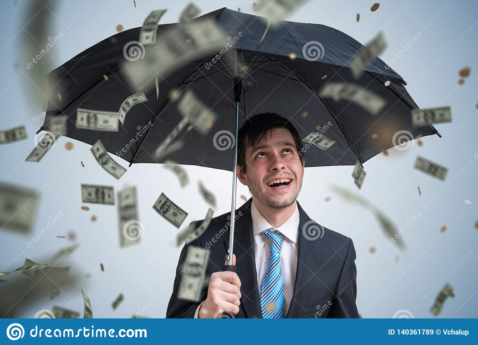 Young successful rich businessman with umbrella and money falling down.