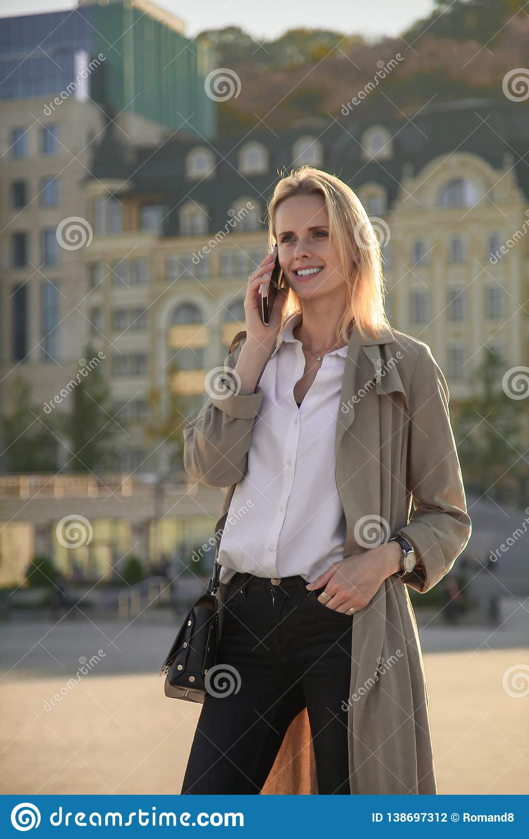 A young successful woman in a trench coat, walking in the street, speaking by her cell phone