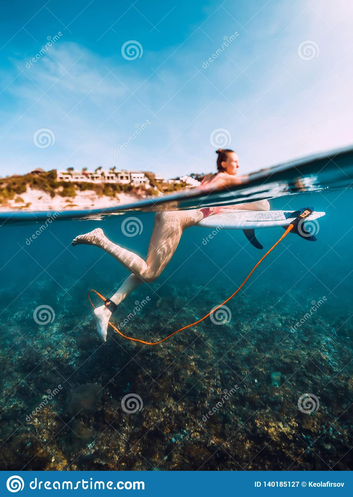 Young surf girl at surfboard underwater in sea