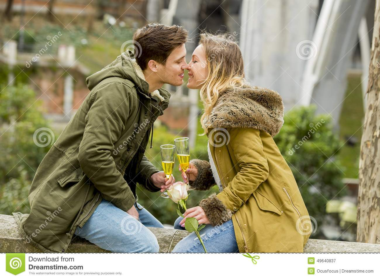 young sweet couple in love kissing tenderly on street celebrating Valentines day or anniversary cheering in Champagne