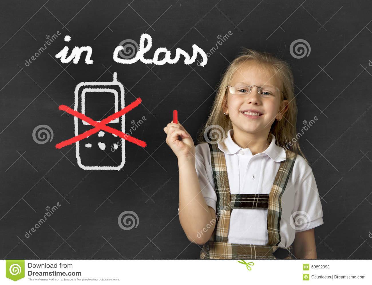 Young sweet junior schoolgirl writing with chalk about not using mobile phone in school class