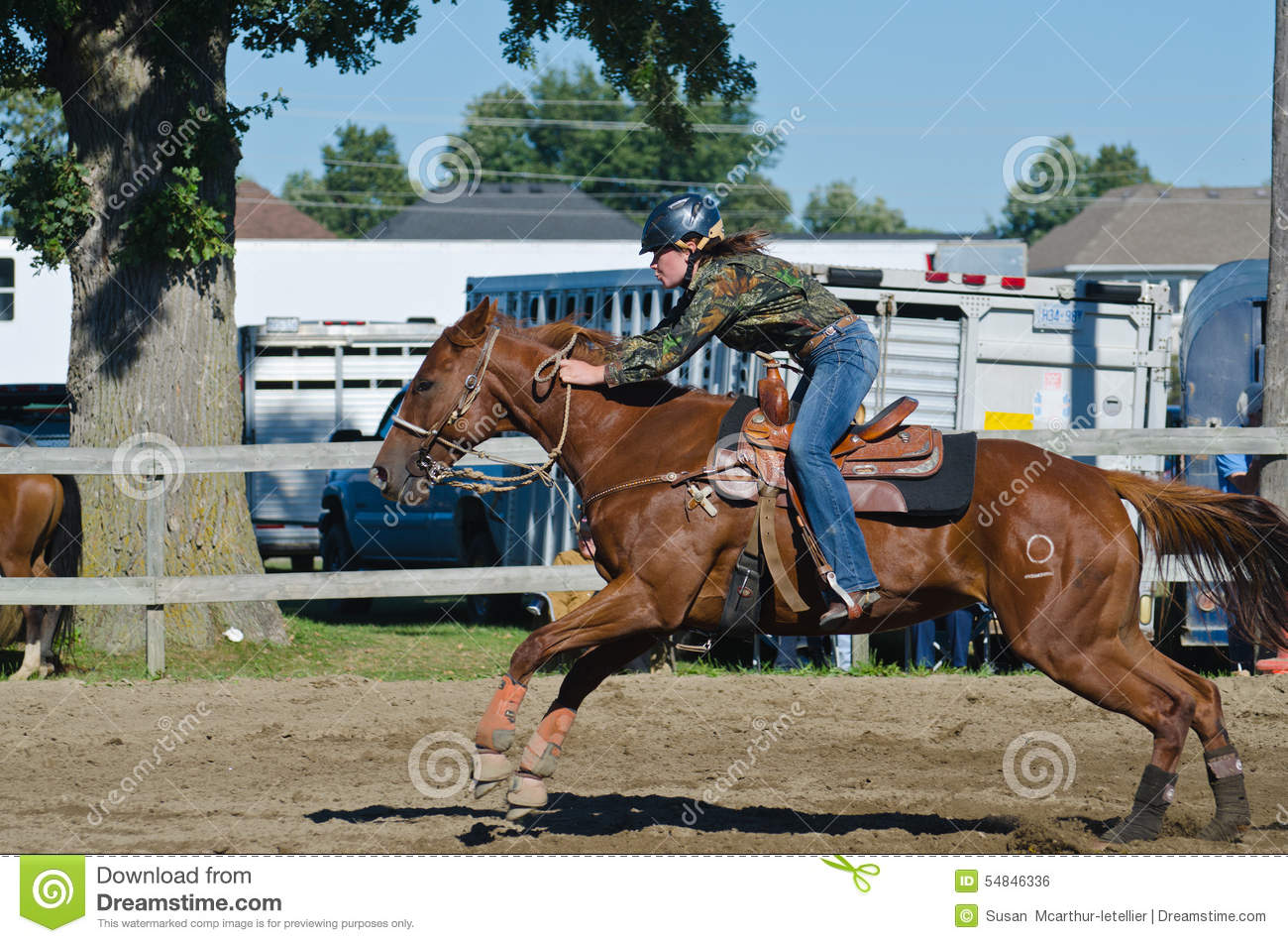 Young teen cowgirl at country fair racing horse