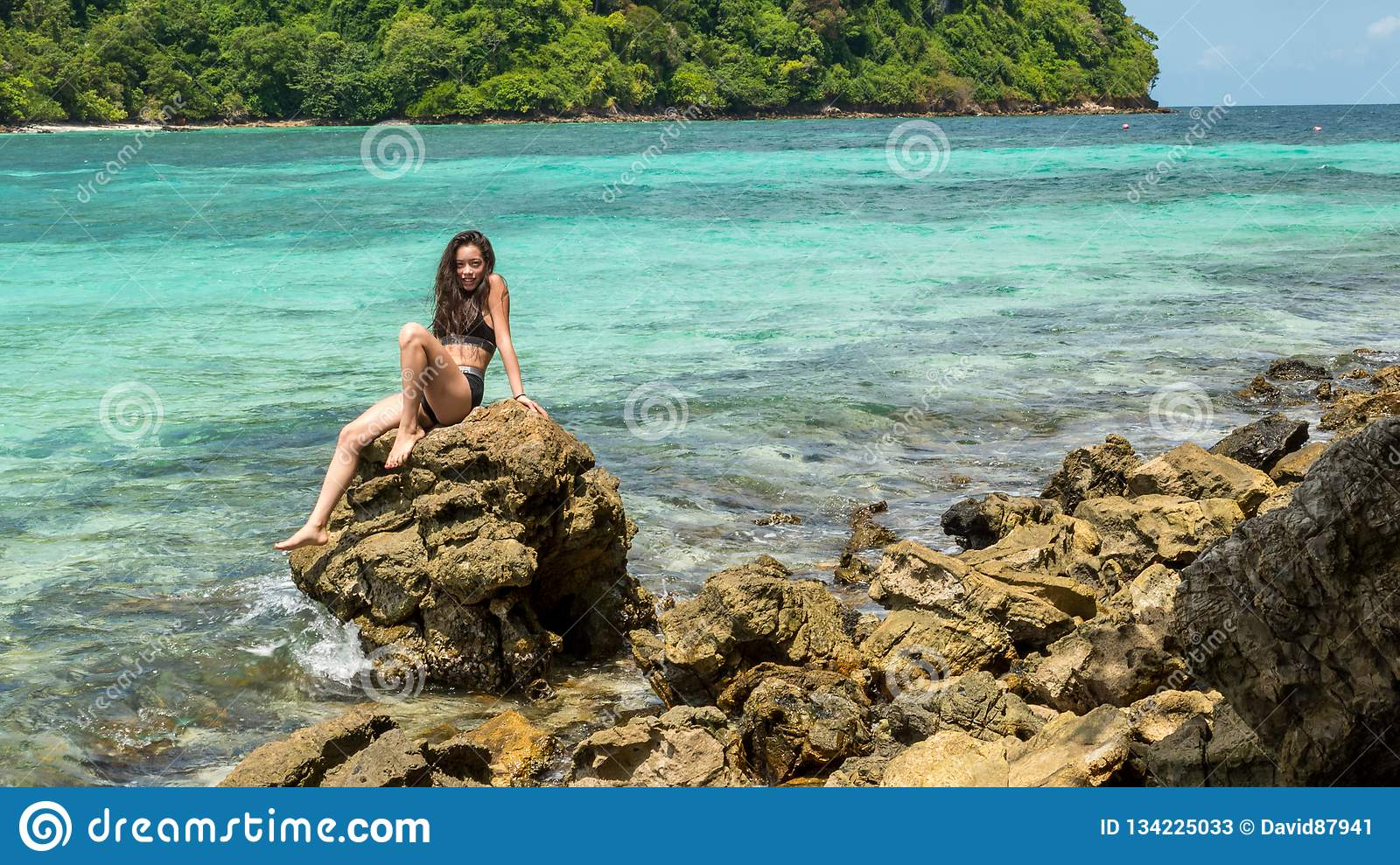 Young teen girl in black bathing suit sitting on rock