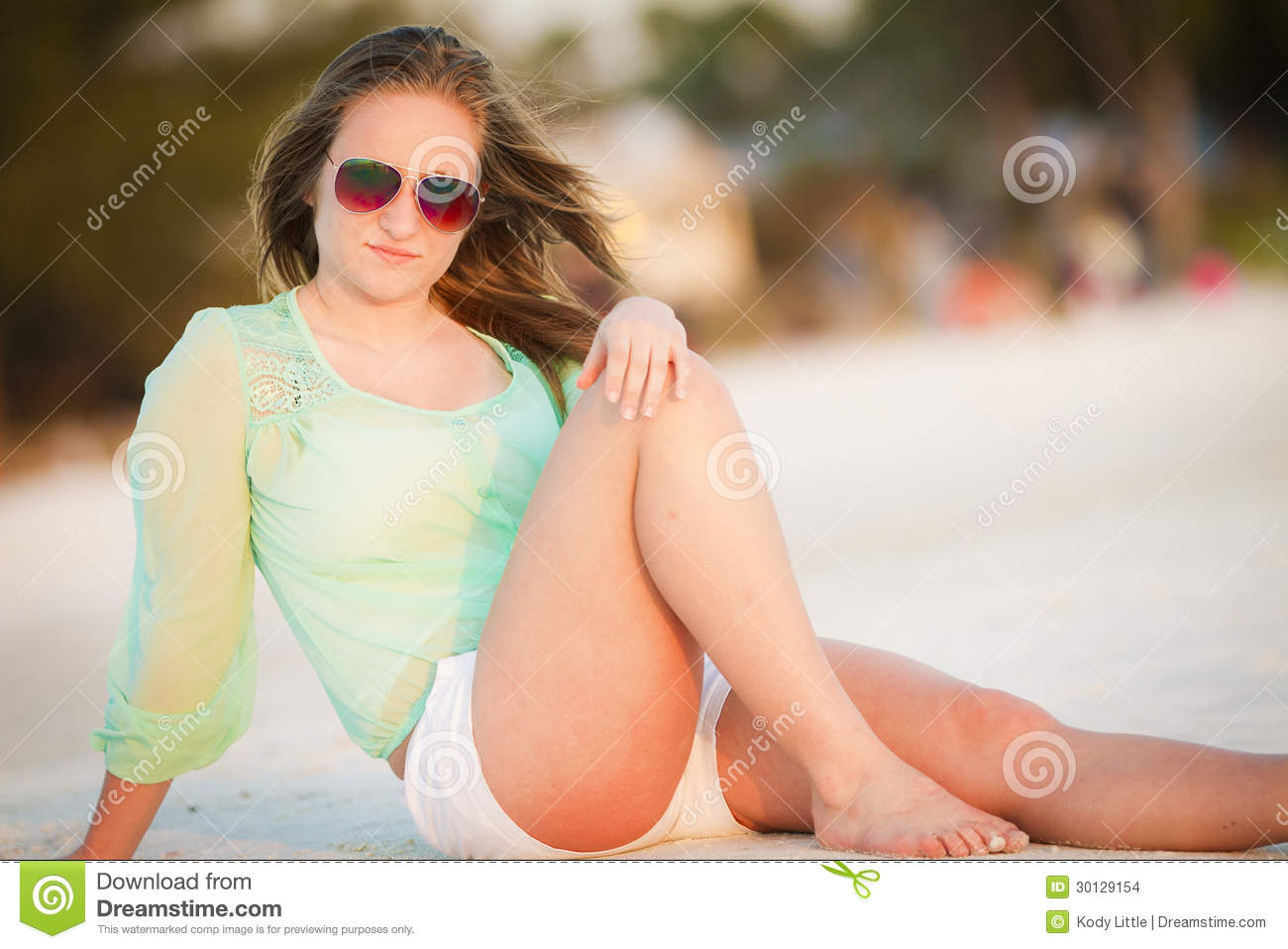 young teen girl enjoying paradise while laying on the beach.