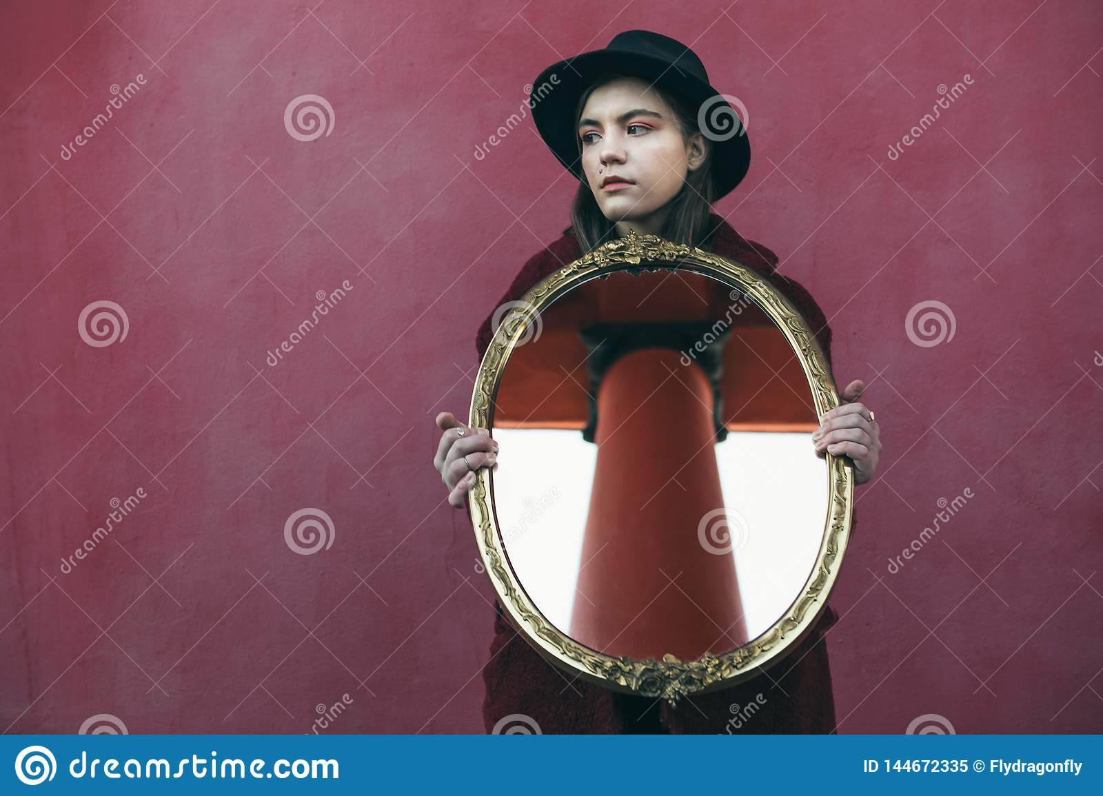 Young teen girl in hat holding mirror in front of red wall. the mirror reflects the column of the building opposite