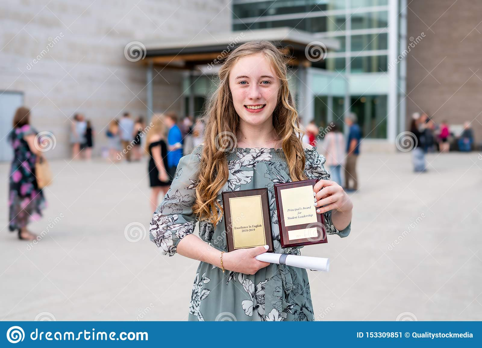 Young Teen Girl/Middle School student standing in front of school with awards and diploma after Grade 8/Middle school graduation c