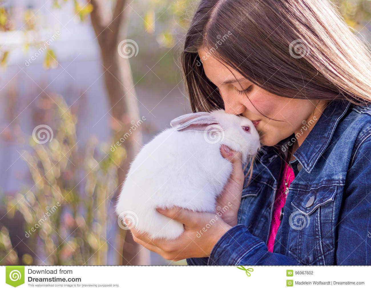 Young teen holding a baby white rabbit kissing it on the forehead