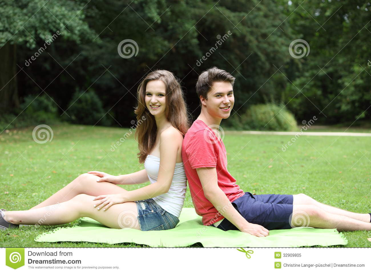 Young Teenage Couple Relaxing In A Lush Green Park Royalty
