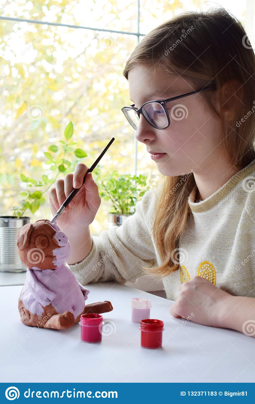 Young teenage girl makes toy, paints clay pig with gouache. Creative leisure for children. Supporting creativity, learning by