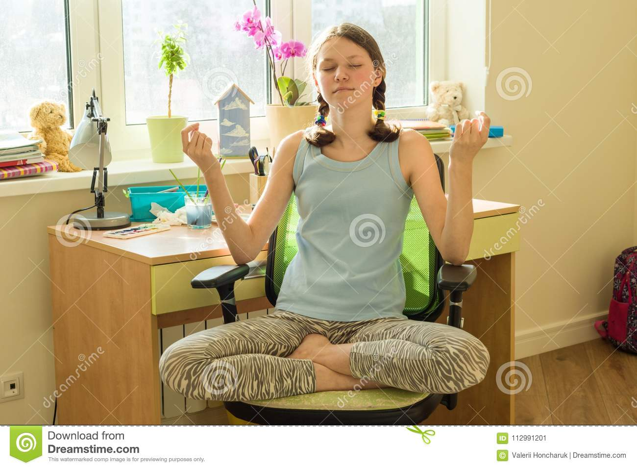 Young teenage girl meditates at home on a chair near the window table, in lotus pose