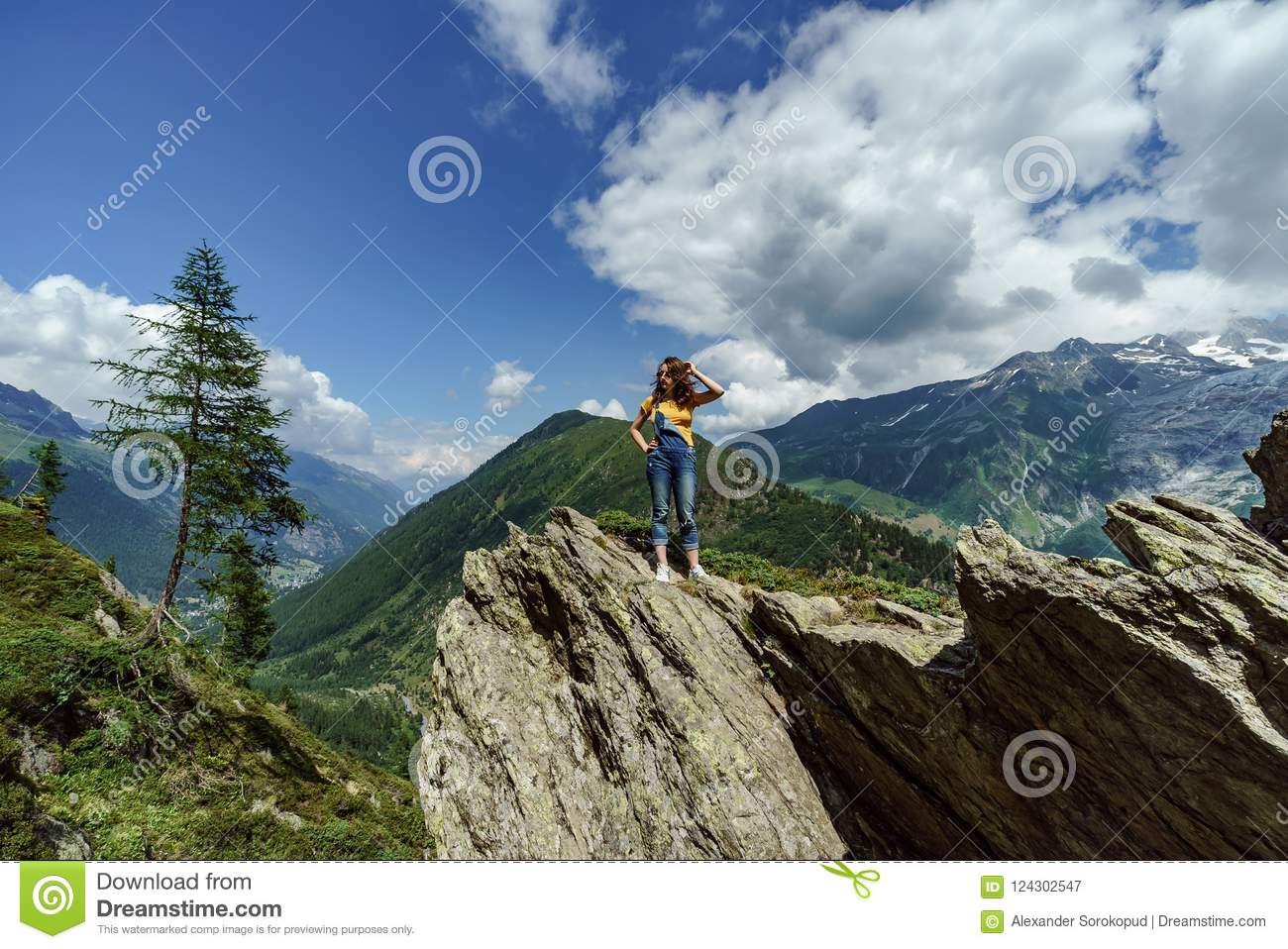 Young teenage girl posing on big stone in Alps