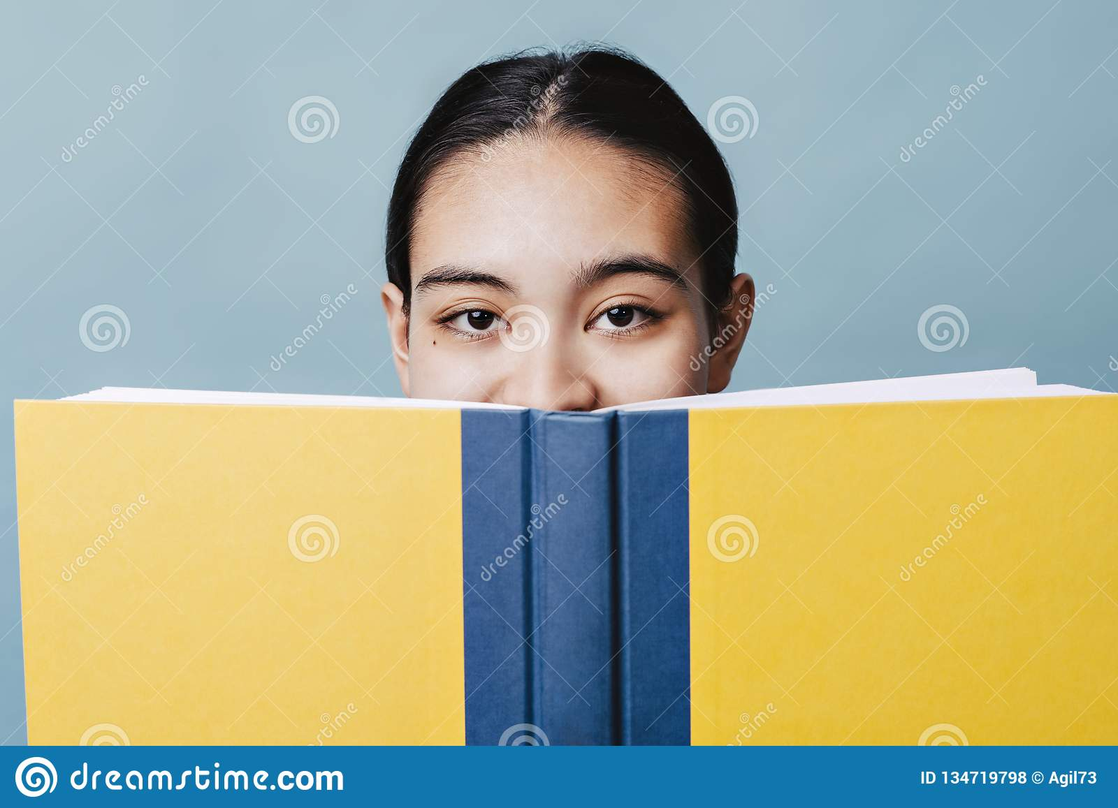 Beautiful Teen Girl Hides Her Smile Behind a Textbook Happy